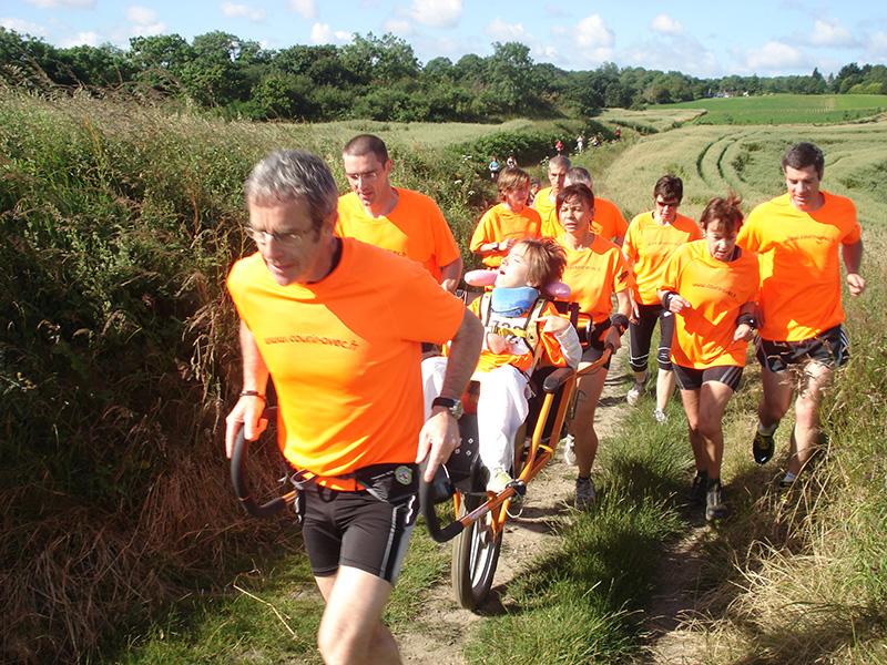 Emmanuelle porté par les équipier de l'association Courir-avec sur le Trail Glazig (2012)
